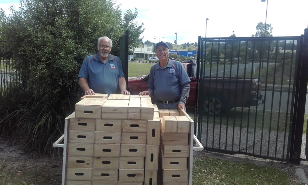 Two of our members handing the building boxes over to the kinder garten